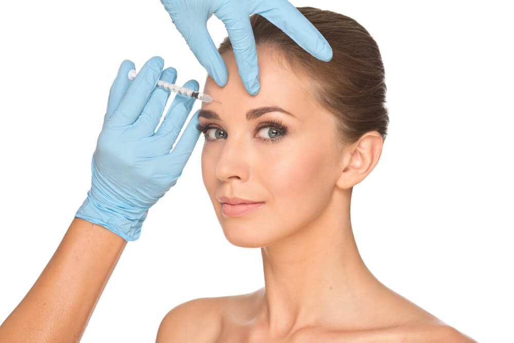 Woman getting BOTOX® injection in the forehead.