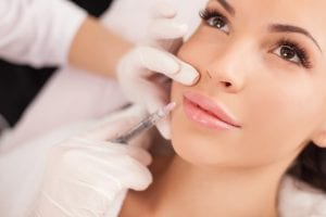 Woman getting botox injections in her face.