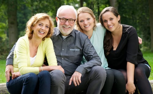 Portrait of a happy family with mother father and two daughters smiling outdoors